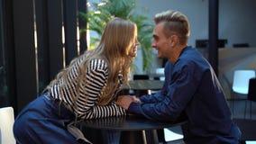El blonde joven encantador se sienta cerca de su hombre en el café y lleva a cabo su oferta de las manos almacen de metraje de vídeo