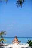 El blonde joven está haciendo yoga en la playa Maldivas Fotografía de archivo