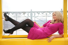 El blonde joven miente en ventana Imagen de archivo libre de regalías