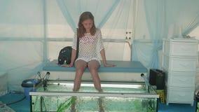 El blonde joven se sienta con las piernas en acuario y consigue la peladura de pescados almacen de video