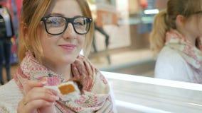 El Blonde liga con la cámara y ofrece la empanada, mujer hermosa en vidrios come atractivo la torta con la crema, gorda almacen de metraje de vídeo