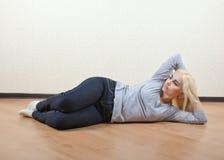 El blonde miente en el piso Fotografía de archivo libre de regalías