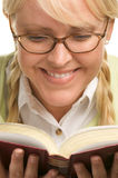 El Blonde sonriente con los Ponytails lee un libro foto de archivo