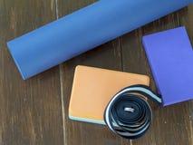 El bloque determinado de la yoga ceñe la estera de la correa en la madera imagenes de archivo