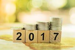 El bloque número de madera 2017 con la pila acuña usando como Año Nuevo del fondo o concepto del negocio Imagen de archivo libre de regalías