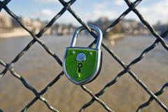 El bloqueo verde está cerrado prendido a una cerca Imagenes de archivo