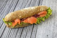 El bocadillo apetitoso miente en un fondo de madera bocadillo en un bollo largo con la ensalada y los salmones fotografía de archivo