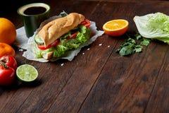 El bocadillo del almuerzo con queso, verduras e hierbas sirvió con la fruta cítrica y el café, foco selectivo, primer, visión sup Imagen de archivo