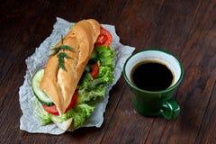 El bocadillo del almuerzo con queso y verduras sirvió con la fruta cítrica y el café, foco selectivo, primer, visión superior Foto de archivo