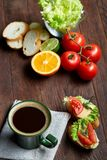 El bocadillo del almuerzo con queso y verduras sirvió con la fruta cítrica y el café, foco selectivo, primer, visión superior Fotografía de archivo