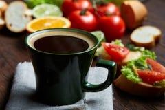 El bocadillo del almuerzo con queso y verduras sirvió con la fruta cítrica y el café, foco selectivo, primer, visión superior Imagen de archivo libre de regalías