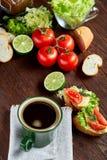 El bocadillo del almuerzo con queso y verduras sirvió con la fruta cítrica y el café, foco selectivo, primer, visión superior Imagenes de archivo
