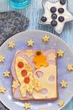El bocadillo divertido con el cohete y un cosmonauta en el queso están en la luna imágenes de archivo libres de regalías
