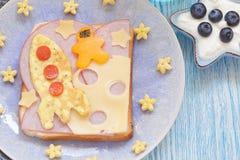 El bocadillo divertido con el cohete y un cosmonauta en el queso están en la luna foto de archivo libre de regalías