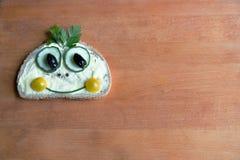 El bocadillo divertido en el tablero de madera foto de archivo