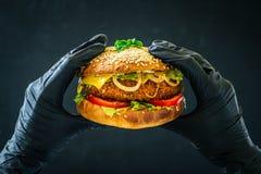 El bocadillo sabroso de la hamburguesa en manos weared el fondo negro de los guantes fotografía de archivo libre de regalías