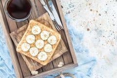 El bocadillo sano con mantequilla de cacahuete, el plátano y el chia crujientes siembra, en bandeja de madera con la taza de café Foto de archivo