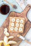 El bocadillo sano con mantequilla de cacahuete, el plátano y el chia crujientes siembra, en el tablero de madera con la taza de c Imágenes de archivo libres de regalías