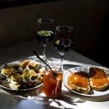 El bocado exquisito con el caviar rojo y el gastrónomo wine Foto de archivo libre de regalías