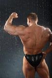 El Bodybuilder se coloca en lluvia de nuevo a cámara Imágenes de archivo libres de regalías