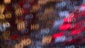 El bokeh borroso colorido de las partículas móviles enciende la inscripción del fondo ho ho ho almacen de metraje de vídeo