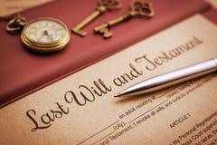 El bolígrafo azul, el reloj de bolsillo antiguo, dos llaves de cobre amarillo y un último y testamento en un cojín de escritorio  imagenes de archivo