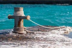 El bolardo oxidado del amarre con las cuerdas de la nave y el mar claro del turquouse ocen el agua en fondo Foto de archivo libre de regalías