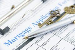 El bolígrafo azul y dos llaves de cobre amarillo del vintage en una solicitud de hipoteca forman Imagenes de archivo