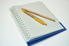El bolígrafo y el lápiz de madera pusieron un cuaderno gris claro del color Imagen de archivo