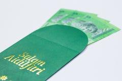 El bolsillo del dinero se da de adulto a los ni?os durante la celebraci?n de Eid Mubarak en Malasia foto de archivo