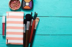El bolso cosmético y compone productos en fondo de madera azul Copie el espacio e imite para arriba Manera del verano Imagen de archivo libre de regalías