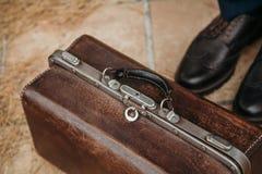 El bolso de cuero está al lado de las piernas del hombre Imágenes de archivo libres de regalías