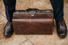 El bolso de cuero está entre las piernas del hombre Imagen de archivo libre de regalías
