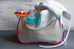 El bolso de las mujeres con los artículos al cuidado para el niño: botella de leche, pañales disponibles, traqueteo, fotos de archivo