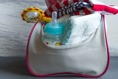 El bolso de las mujeres con los artículos al cuidado para el niño: botella de leche, pañales disponibles, traqueteo, pacificador imagenes de archivo