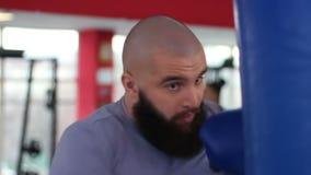 El bolso de perforación del boxeo del hombre joven, atleta profesional acaba el entrenamiento activo almacen de metraje de vídeo