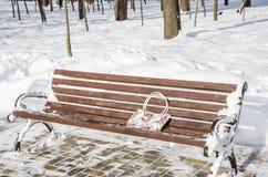 El bolso de una mujer olvidada en un banco viejo en el parque en el invierno imagenes de archivo