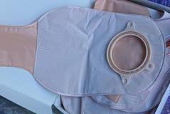 El bolso médico plástico de la operación del intestino grueso miente en una caja de papel gris imágenes de archivo libres de regalías