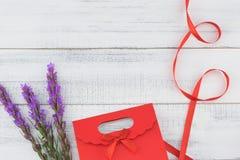 El bolso rojo del regalo adornado con el liatris violeta florece Fotos de archivo