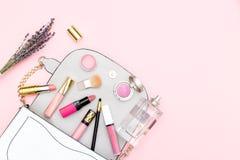 El bolso y los cosméticos femeninos fijaron en un fondo rosado Copie el SP Imagen de archivo