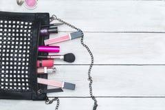El bolso y los cosméticos femeninos mienten en un fondo de madera la plano Imágenes de archivo libres de regalías
