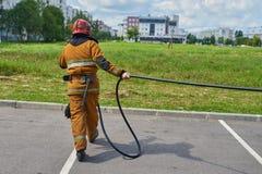 El bombero de sexo masculino tira de la manguera fotos de archivo libres de regalías