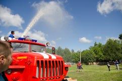 El bombero en el coche de bomberos vierte el agua del cañón del fuego en participantes alegres en competencias aficionadas foto de archivo
