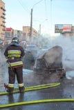El bombero está cerca de coche quemado en la calle de la ciudad Imagen de archivo libre de regalías