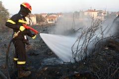 El bombero extingue el fuego en un campo por la inundación del agua Fotografía de archivo
