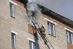 El bombero extingue un fuego en el apartamento Imagen de archivo libre de regalías