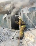 El bombero extingue una casa de madera en Imagenes de archivo