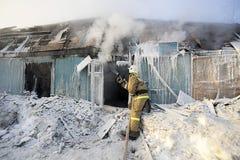 El bombero extingue una casa de madera en Imágenes de archivo libres de regalías