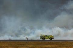 El bombero lucha el fuego bajo que cierra el aeropuerto internacional de San Salvador Imagen de archivo libre de regalías