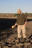 El bombero militar con un detector de metales examina el suelo en el campo para la presencia de minas imágenes de archivo libres de regalías